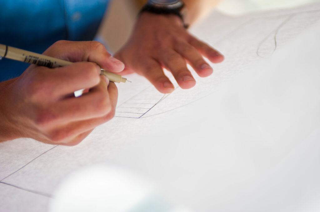 Hands hold a pen while drawing a design on a sheet of paper.
