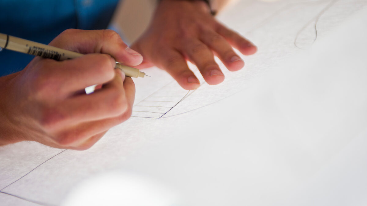 Hands hold a pen and paper while drawing a design.